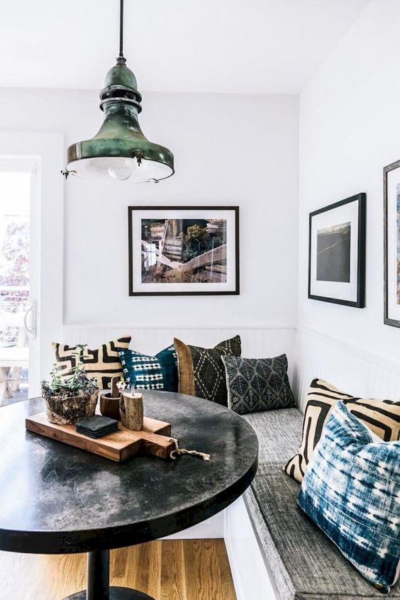 a boho dining nook with printed pillows, a black round table and a metal pendant lamp