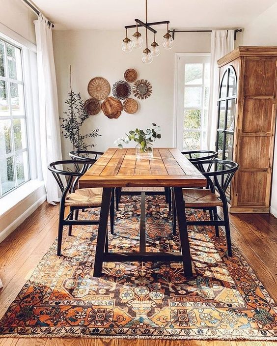 a boho dining room with a beautiful Eastern rug, an arrangement of decorative plates, a wooden table and wicker chairs