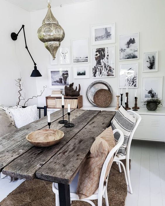 a boho dining space with a rough wooden table, a Moroccan lantern over the space and a gallery wall