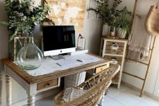 a boho eclectic home office with a vintage desk, a rattan chair, a jute rug, a ladder, sunburst mirrors, a lot of greenery and a map