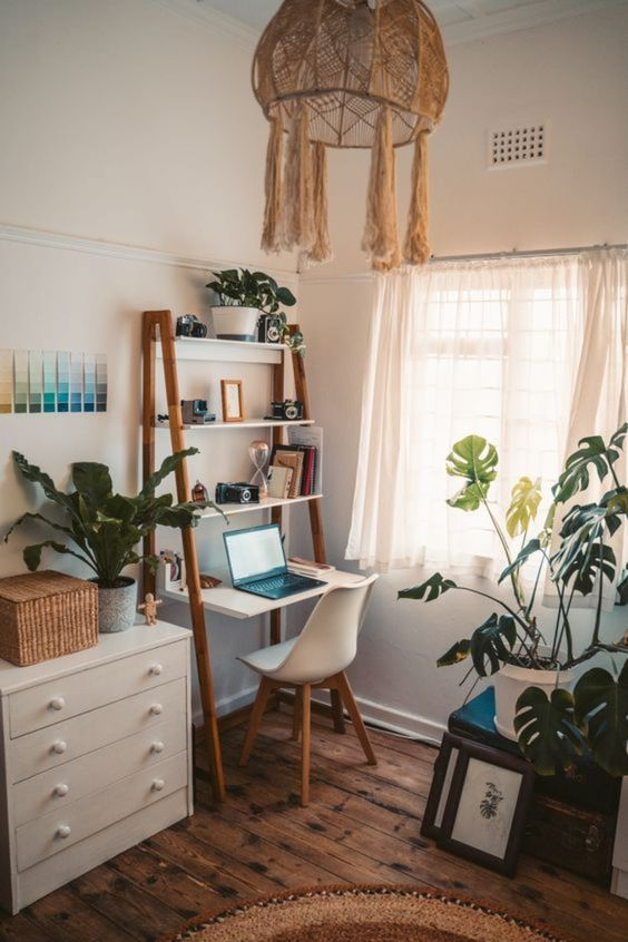 a boho home office nook with a small desk with shelves, a dresser with a basket and potted plants, a woven chandelier and a white chair