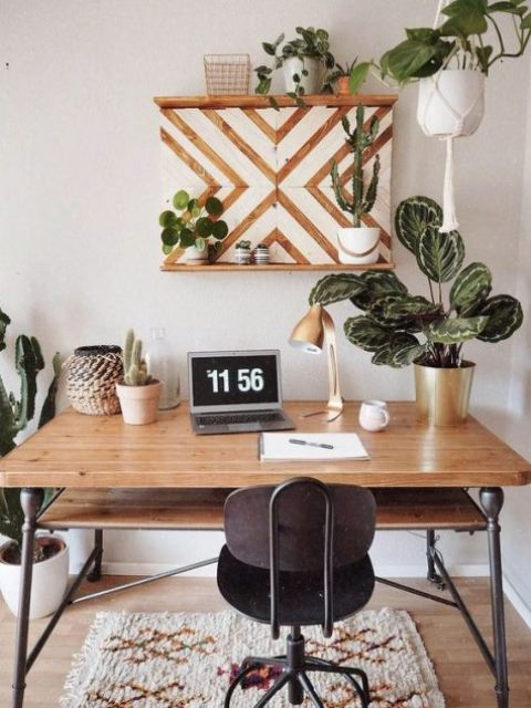 a boho home office nook with an industrial wood and metal desk, a black metal chair, a chevron shelving unit and potted plants