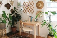 a boho home office nook with hats and decorative baskets, potted plants, a boho rug, a simple desk and a leather chair