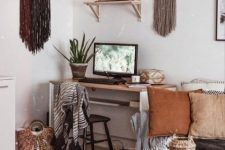 a boho home office with long fringe hanging, a sleek desk, lots of basket for storage and earthy tone pillows