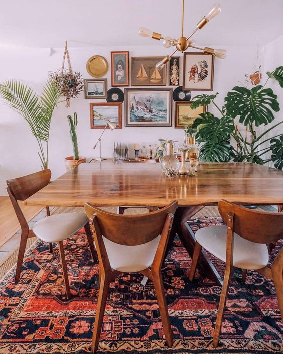 a boho meets mid century modern space with a cool rug, chic wooden furniture, a gallery wall and potted greenery and palms