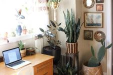 a boho mid-century modern home office with a stylish desk, a white chair, potted plants, a gallery wall and hanging planters