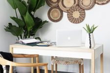 a boho tropical home office with a sleek desk, woven chairs, potted plants, decorative plates on the wall is very airy and cool