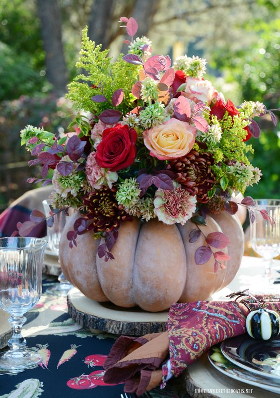 a bold fall centerpiece of a chalky pumpkin, usual and dark foliage, bright blooms is very bright