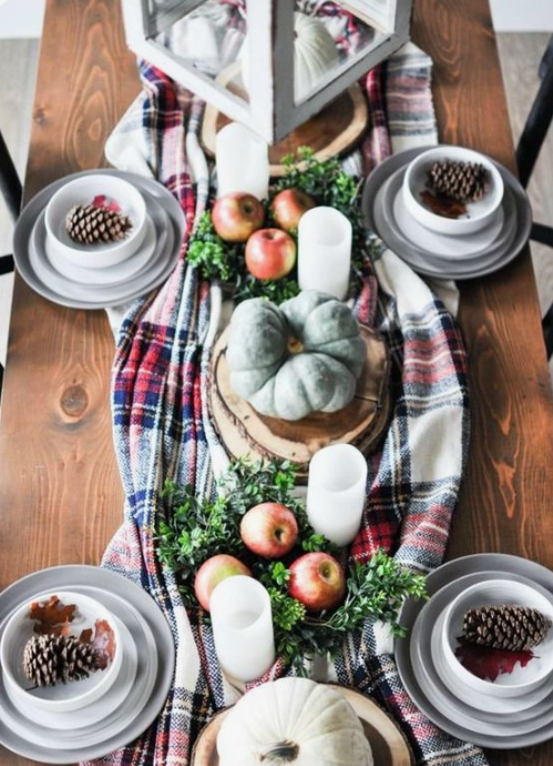a bold fall tablescape with a plad runner, greenery, apples, heirloom pumpkins candles and pinecones