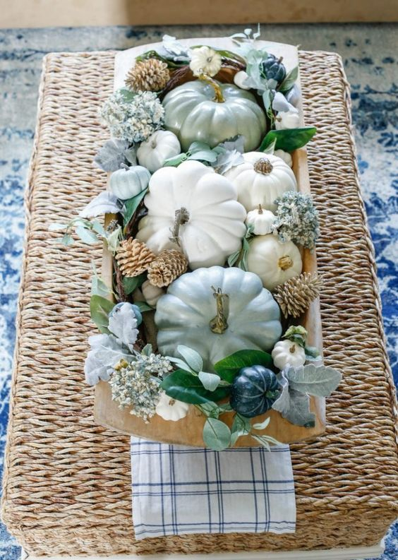 a bread bowl with neutral and pastel pumpkins, blue blooms, bleached pinecones and pale and usual foliage for the fall
