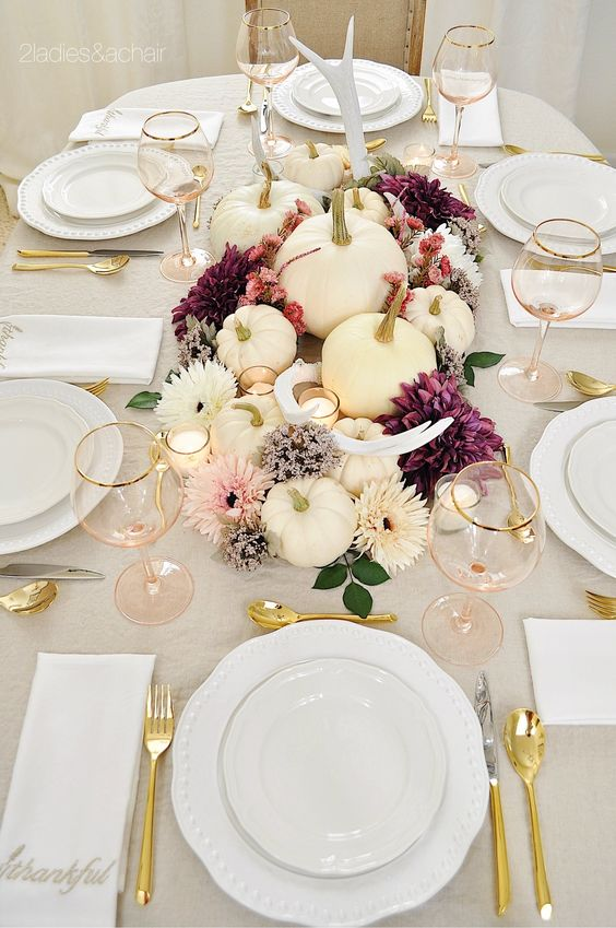a bright and chic fall centerpiece of white and purple blooms, antlers, candles and foliage plus white pumpkins