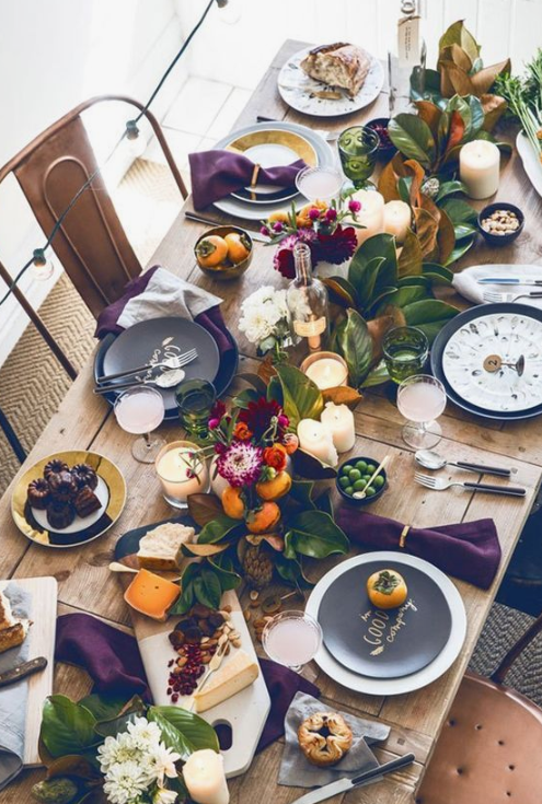 a bright and natural fall tablescape with fall fruits, blooms, foliage, pillar candles and printed dark plates