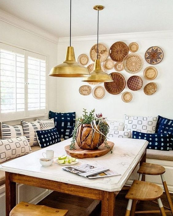 a bright boho dining space with an arrangement of decorative plates, pendant lamps, colorful printed pillows