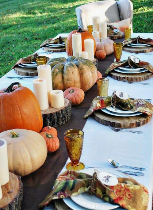a bright fall table with a brown runner, wood slice placemats, natural pumpkins and pillar candles