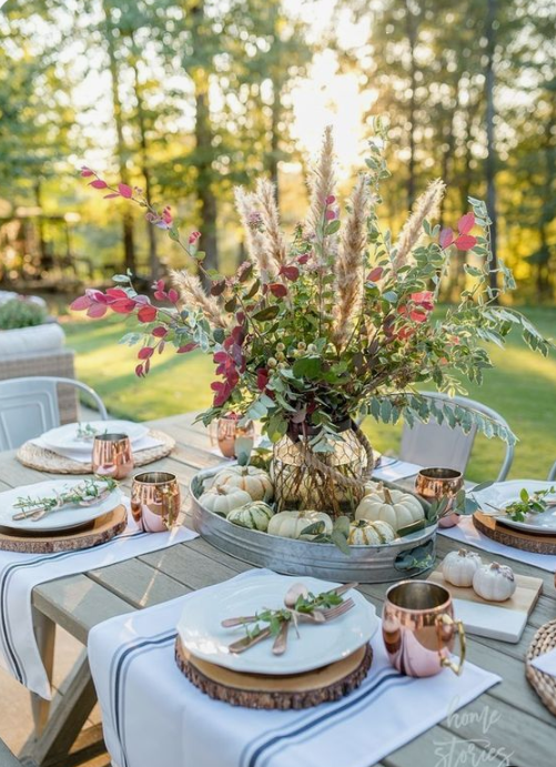 a chic fall tablescape with a greenery, herb and foliage centerpiece, wood slices, copper mugs, striped placemats and natural pumpkins