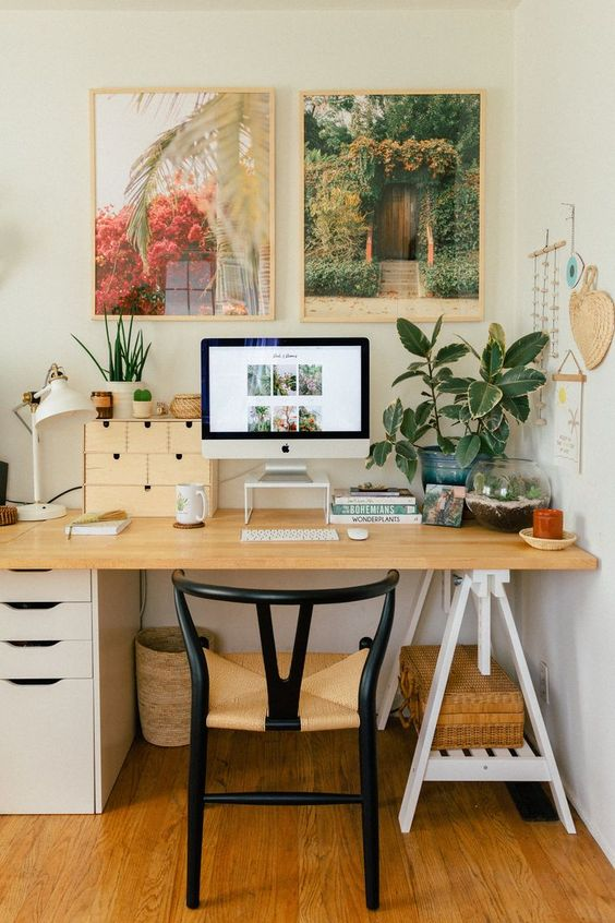 a chic mid-century modern boho home office with a desk, a chic chair, a tropical gallery wall and potted plants