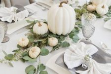 a chic white fall tablescape with white linens, white pumpkins, catchy plates, greenery and mini pumpkins