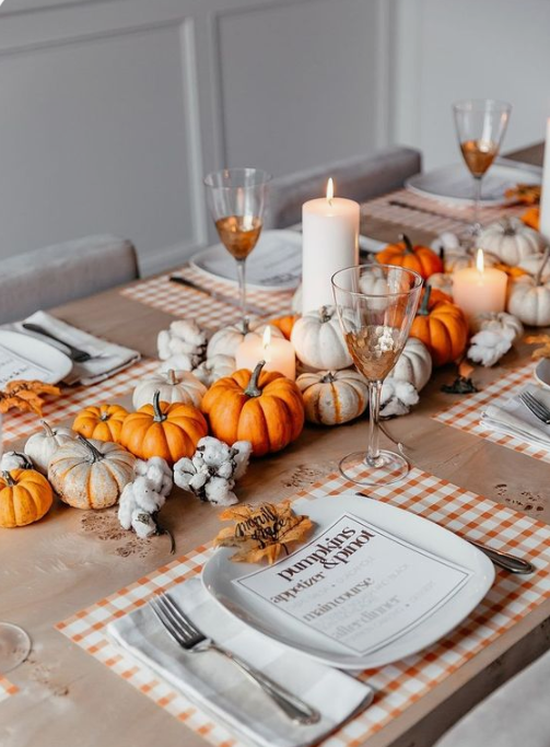 a colorful fall table with plaid placemats, bright pumpkins and cotton, pillar candles and fall leaves instead of place cards