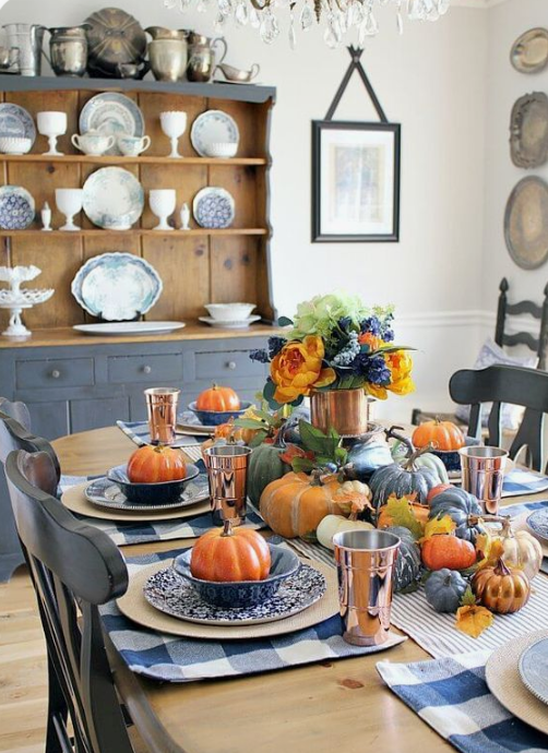 a colorful fall tablescape with a striped runner and plaid placemats, colorful pumpkins and copper mugs and vases