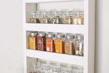 a compact open shelf with spices in jars is a cool spice rack idea that will be useful in any kitchen