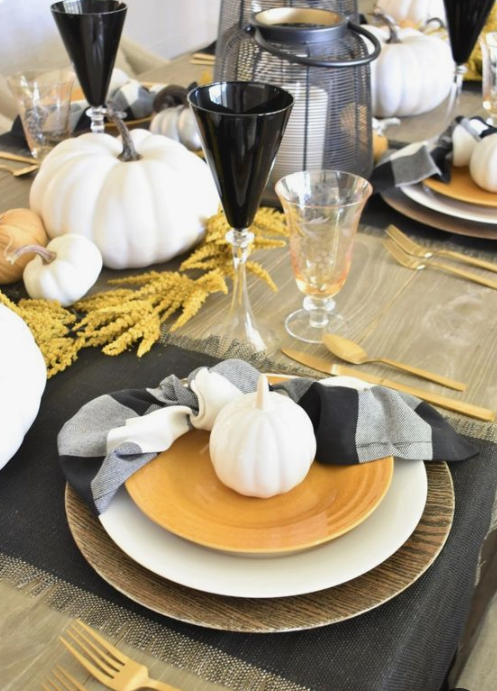 a contrasting fall tablescape with printed textiles, black glasses, wheat, white pumpkins and gold cutlery