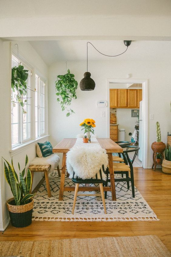 a cozy boho dining nook with simple wooden furniture, a tassel rug, greenery and a wicker lamp hanging over the table