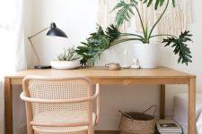 a cozy boho home office nook with a sleek desk, a rattan chair, a boho rug, a basket and a macrame hanging plus potted plants