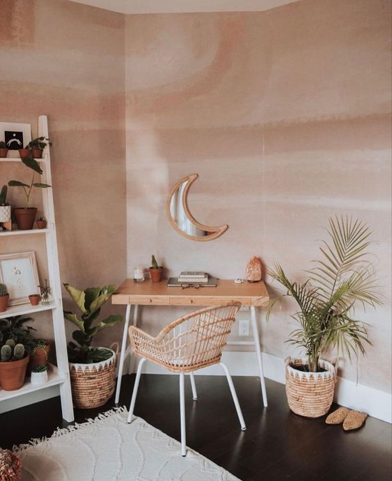 a cozy boho home office nook with a small desk and a rattan chair, potted plants, a ladder with plants and cacti, a neutral rug