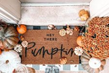 a cozy fall porch with lots of pumpkins, gourds and leaves, bright fall blooms and layered mats