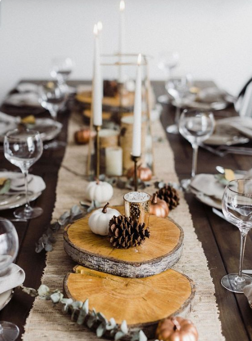 a cozy fall table setting with a fabric runner, wood slices, pinecones, candles and mini pumpkins
