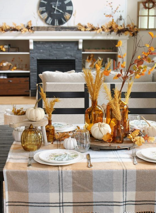 a cozy fall tablescape with a plaid tablecloth, amber glasses and bottles, white pumpkins and fall leaf and herb arrangements