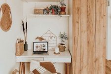 a cozy neutral boho home office nook with a desk, a patchwork chair, a catchy hanging and open shelves plus a storage piece