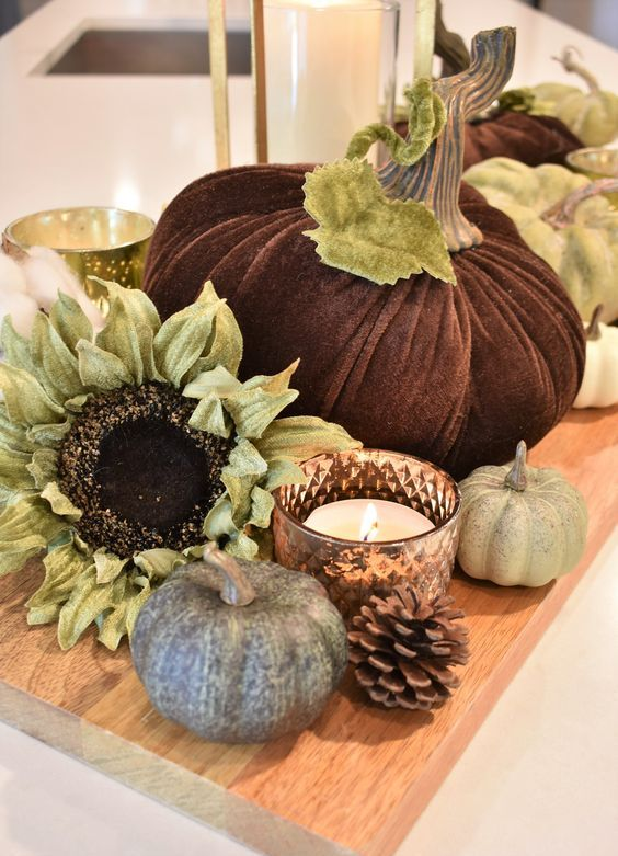 a cutting board with fake pumpkins, blooms, candles and pinecones for durable rustic decor