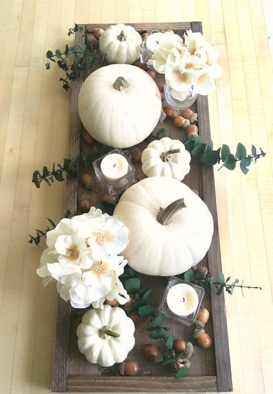 a dark stained woodne tray, white pumpkins, blooms, candles and acorns for a pretty fall centerpiece