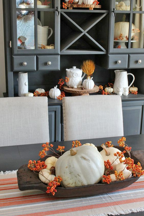 a dough bowl with berries and white pumpkins, and similar decor on the buffet behind