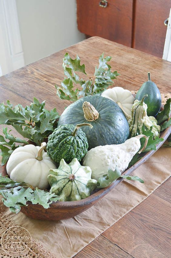 a dough bowl with pumpkins and gourds and foliage is a cool fall all-neutral centerpiece