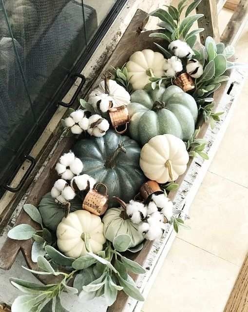 a dough bowl with pumpkins, real and faux ones, cotton, greenery and copper mugs is a chic and stylish arrangement to decorate a space