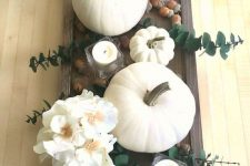 a fall centerpiece of a dark tray with white candles, white blooms and pumpkins, acorns and eucalyptus