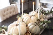a fall centerpiece of a table runner, pumpkins, gourds, antlers, candles and beads is veyr lush and chic