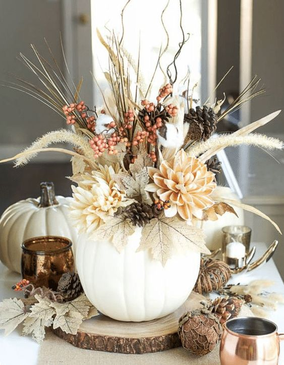 a fall centerpiece of a white pumpkin as a vase, dried leaves, blooms, twigs, berries and wheat