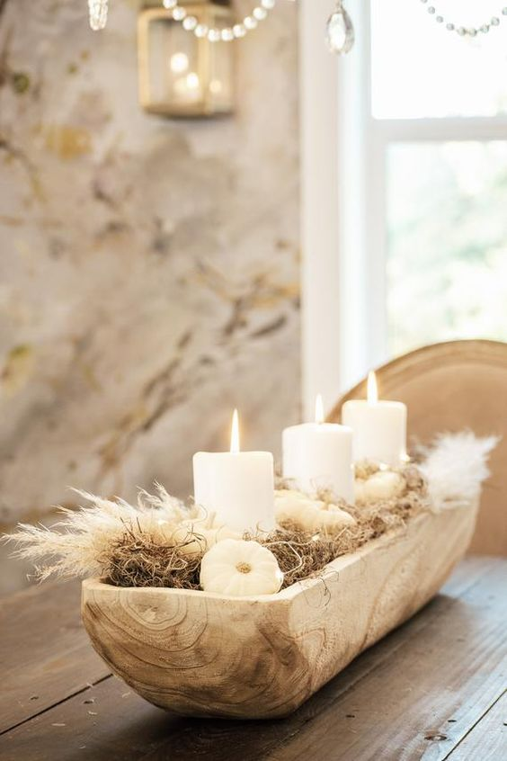 a fall centerpiece of a wooden box with hay, pampas grass, pumpkins and pillar candles is very stylish