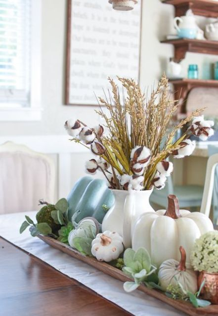 a fall centerpiece with fake pumpkins, greenery, succulents, herbs and cotton in a simple white jug