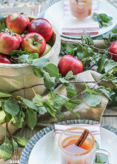 a fall tablescape with foliage, apples, burlap and blue chargrers plus fall drinks