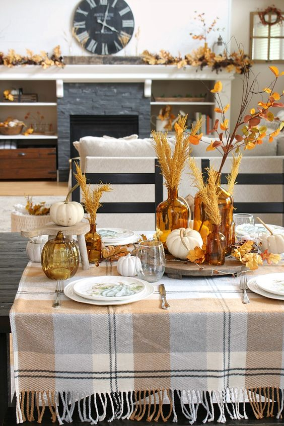 a fall tablescape with pumpkins, leaves, wheat on stands and trays looks very inviting and very cozy