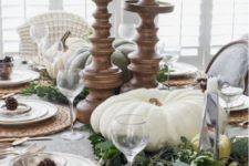 a famrhouse tablescape with heirloom pumpkins, greenery, woven placemats, pinecones and candles in tall wooden candleholders