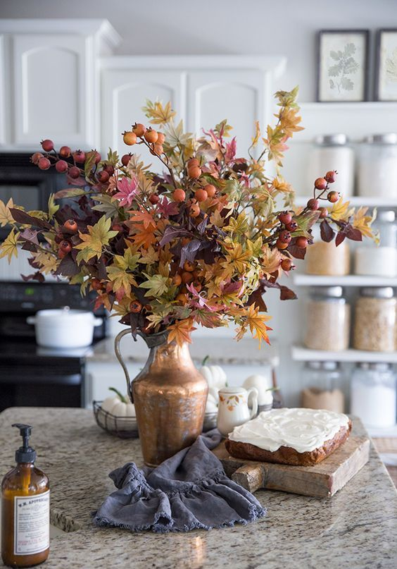 a fantastic and bright fall leaf and berry attangement in a metallic vase is an amazing idea