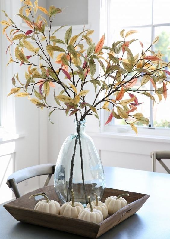a farmhouse centerpiece of a wooden tray with pumpkins, a glass vase with branches and leaves is a chic and easy idea