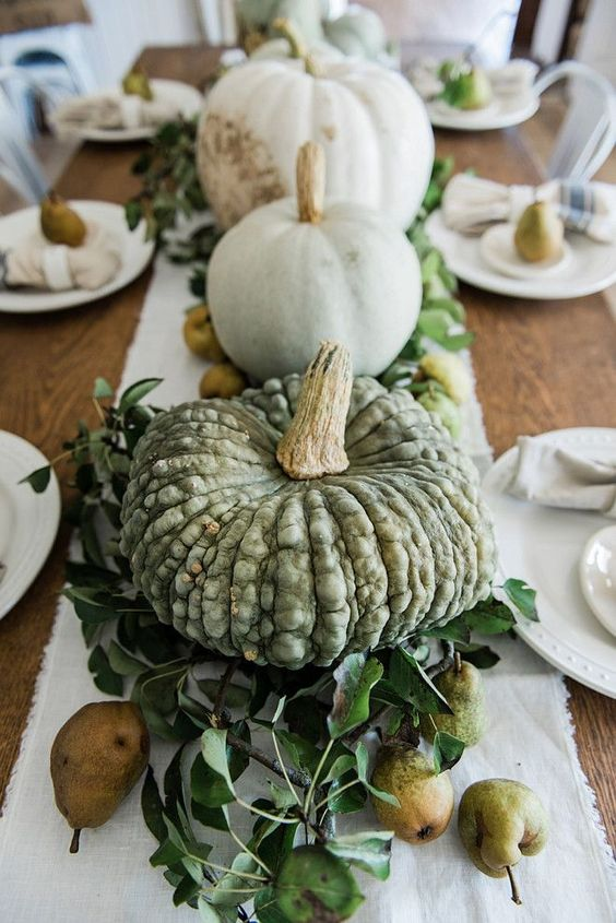 a farmhouse fall centerpiece of various pumpkins, foliage and pears is harvest-loving and very fall-like piece