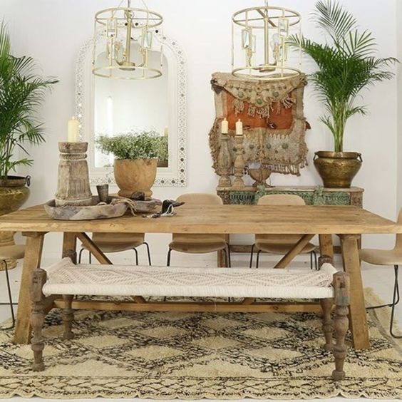 a free-spirited dining room with catchy pendant lamps, carved wooden furniture and a macrame bench