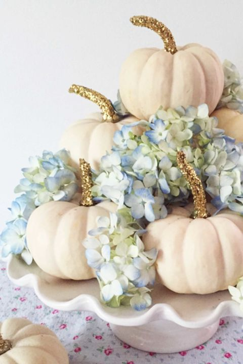 a glam fall centerpiece of a white stand with white pumpkins and gold glitter and blue hydrangeas is chic